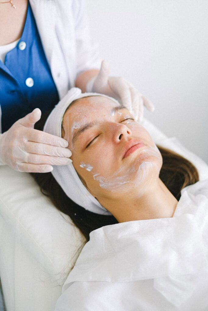 crop beautician massaging client face with lotion during spa procedures